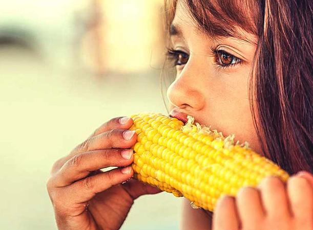 Девочка кушает кукурузу